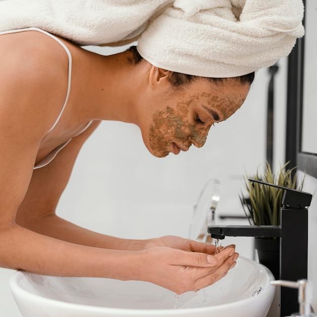 Donna che si lava il viso dopo aver indossato una maschera fatta in casa
