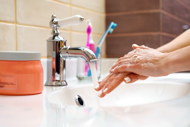Woman washing her hands with soap close up