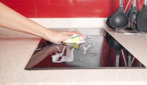 キッチンでモダンな電気ストーブを洗う女性。