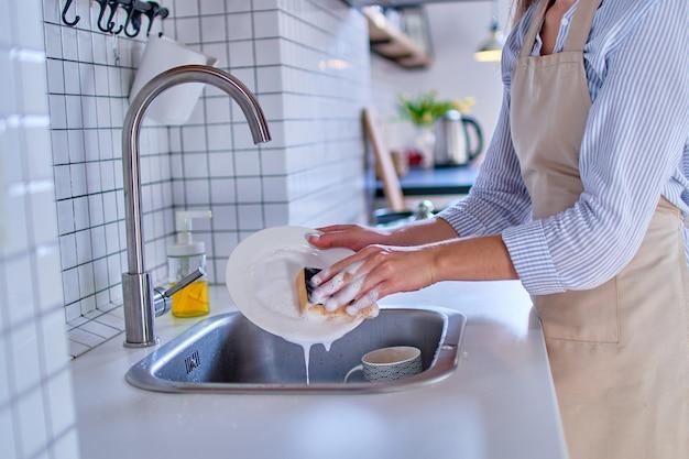 Женщина, моющая тарелку в белой современной кухне крупным планом