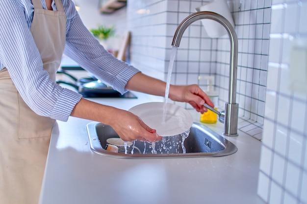 白いモダンなキッチンのクローズアップでプレートを洗う女性