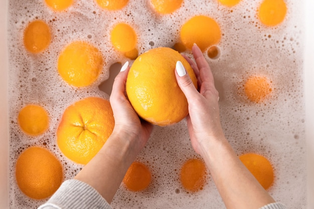 Woman washing ripe orange, grapefruit under faucet in the sink kitchen, soaking fruits in soapy water thoroughly washes after store.