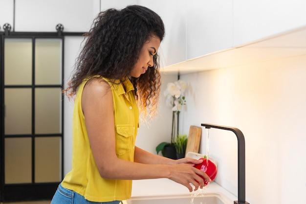 Женщина моет посуду дома