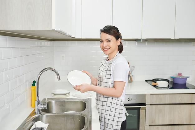 Женщина моет посуду на кухне
