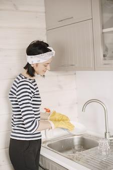 ゴム手袋で皿を洗う女性。