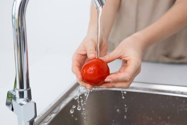 Woman washing tomato with tap water