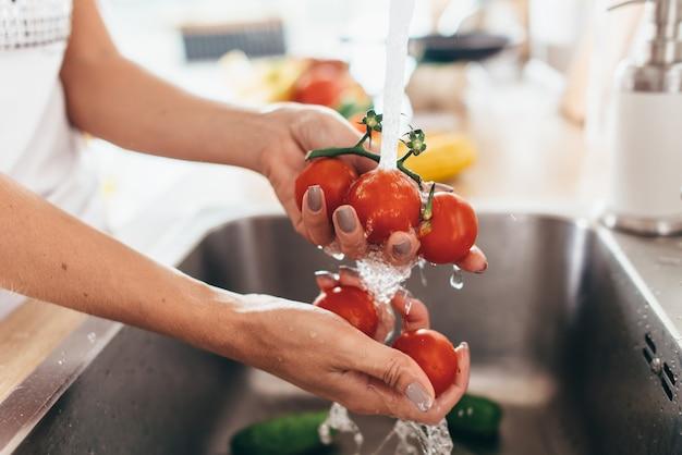 부엌 싱크대에 토마토를 세척하는 여자를 닫습니다.