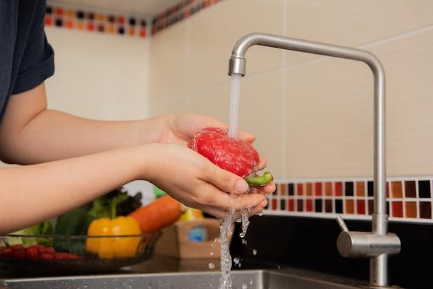 近代的な台所のインテリアでシンクするために近くのワークトップで野菜を洗う女性