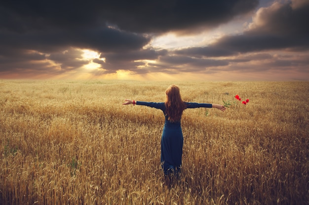 Woman watch sunset in a field with arms outstretched