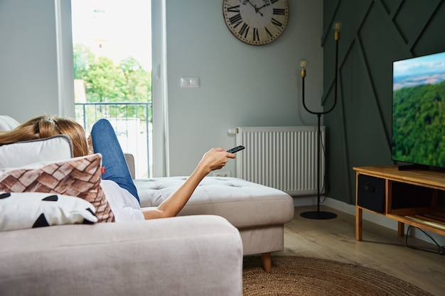 Woman watch tv set while luying on the sofa and switch channels with remote control