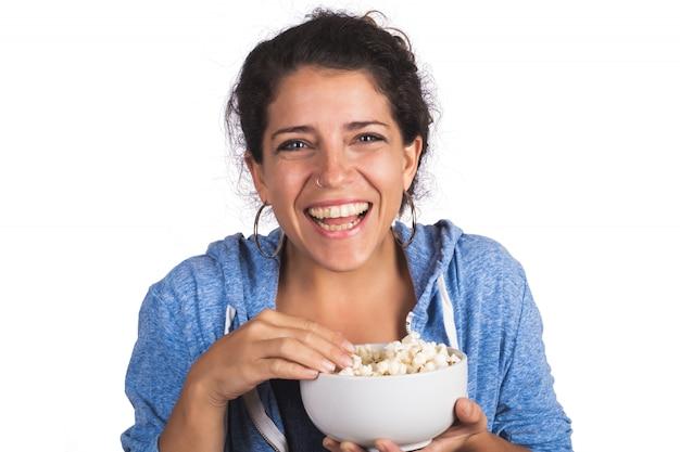 팝콘을 먹는 동안 영화를 보는 여자.