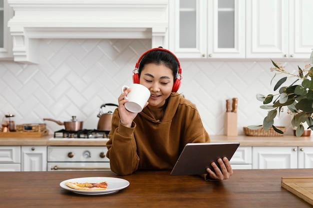 태블릿에 비디오를보고 커피를 마시는 여자