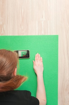 Woman watching fitness training lessons in smartphone sitting on green exercise mat at home, top view.