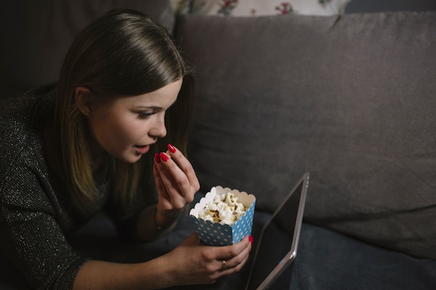 タブレットで面白い映画を見ている女性