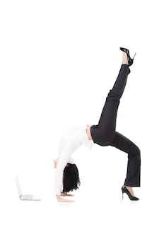 Woman watching the laptop doing a handstand bridge