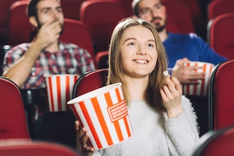 Woman watching movie near men