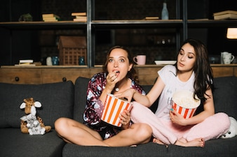 Woman watching movie while her friend taking popcorn from her bucket