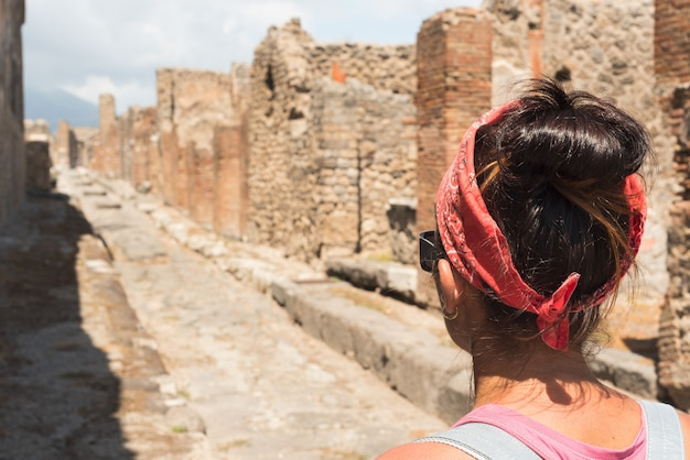 Woman watching the roman archaeological site of pompeii, in italy.