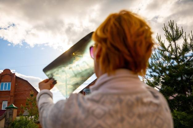 X線画像を通して日食を見ている女性