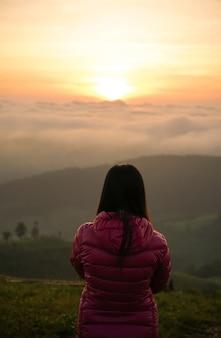 언덕에서 혼자 일출을보고하는 여자