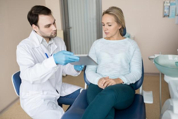 Таблетка женщины наблюдая с дантистом