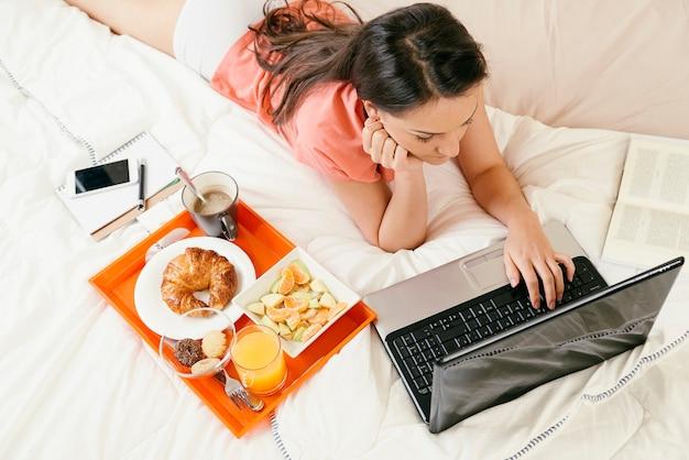 Женщина смотрит портативный компьютер и завтракает. она в спальне. вид сверху