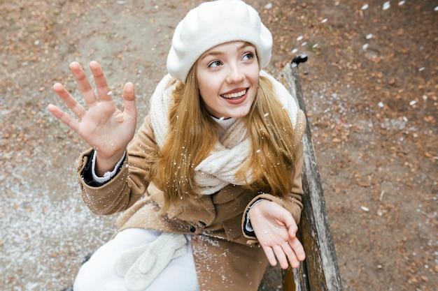 Женщина смотрит на снегопад, сидя на скамейке в парке