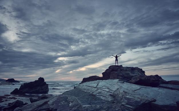 해변에서 석양을보고하는 여자. 갈리시아 해안에 catedrales 해변