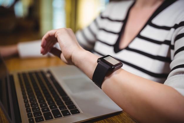 Donna che guarda il tempo sul smartwatch mentre si utilizza laptop