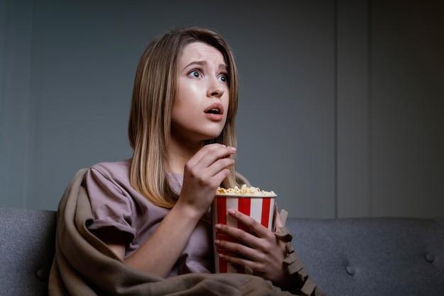 Женщина смотрит телевизор и ест попкорн