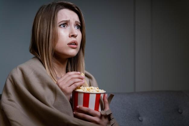 Donna che guarda la tv e mangia popcorn