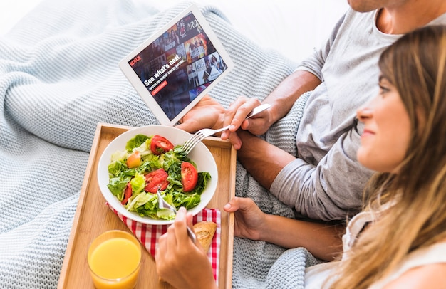 Woman watching tv series and eating salad with boyfriend