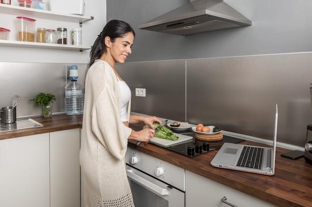 ビデオを見て、家で料理をする女性
