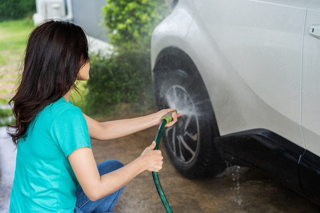 Woman water spray her car wheel with water tube washing it