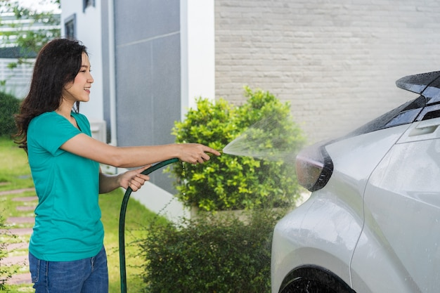 Woman water spray her car with water tube washing it
