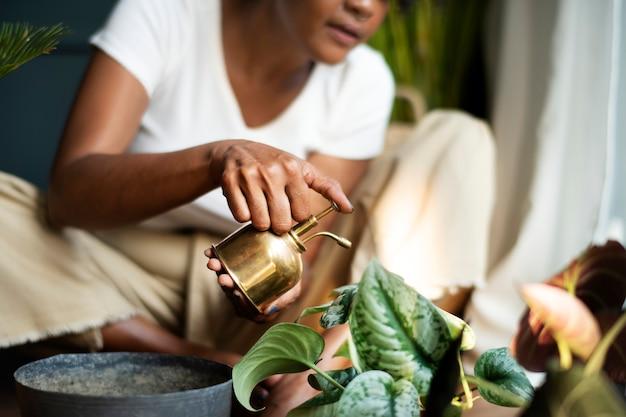 집에서 식물에 물을 주는 여자