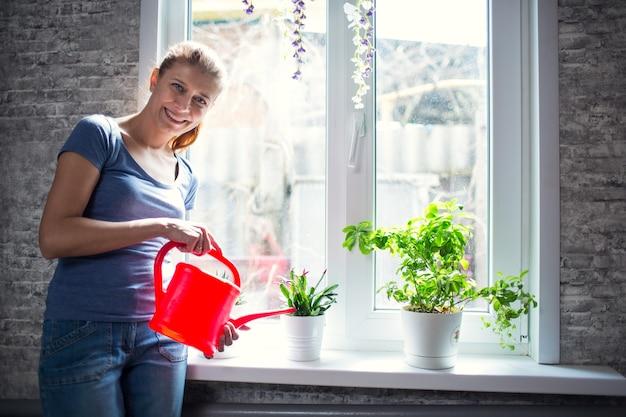 Женщина поливает цветы дома на окне