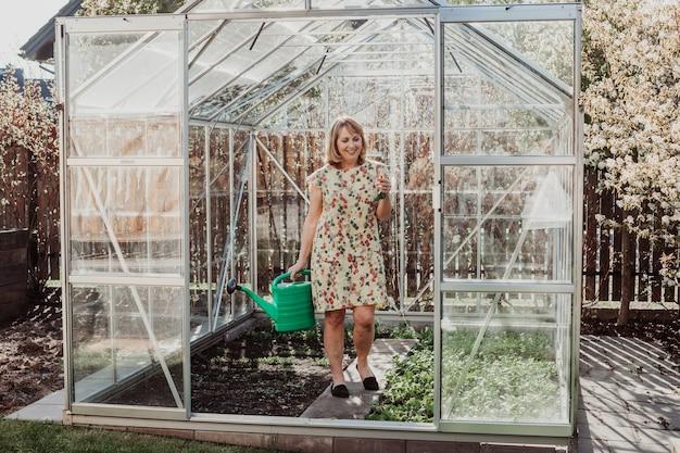 온실에서 녹색 물을 깡통으로 정원에 물을주는 여자