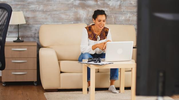 Женщина машет своим коллегам во время видеозвонка, работая дома, сидя на диване.