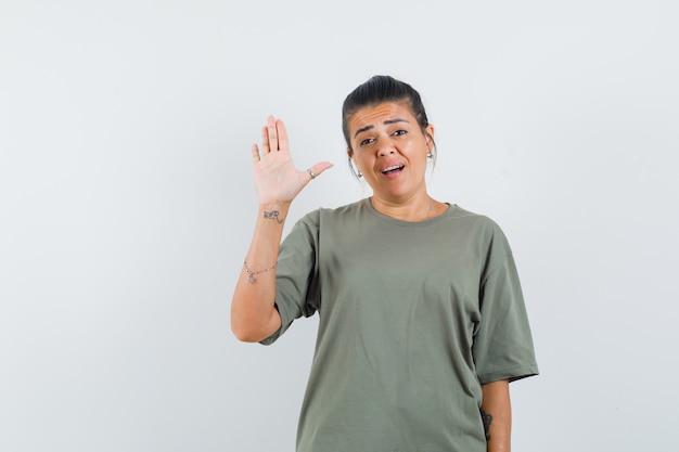 Женщина машет рукой для приветствия в футболке и выглядит уверенно
