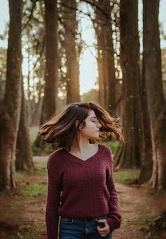 森の中で髪を振る女性