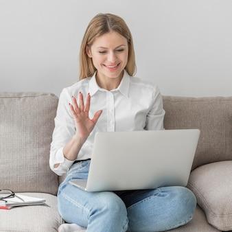 Женщина машет в своем классе онлайн