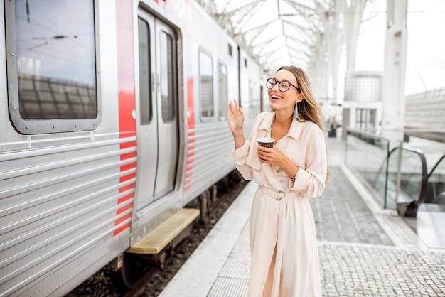 Женщина машет рукой прощаясь возле поезда на вокзале