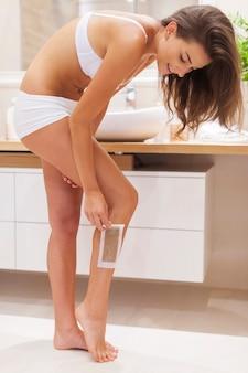 Woman waxing leg in bathroom