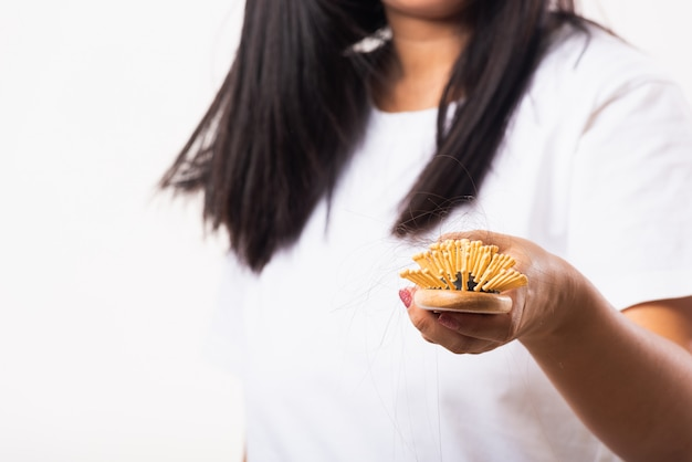 Woman weak hair she shows hairbrush with damaged long loss hair in the comb brush on hand