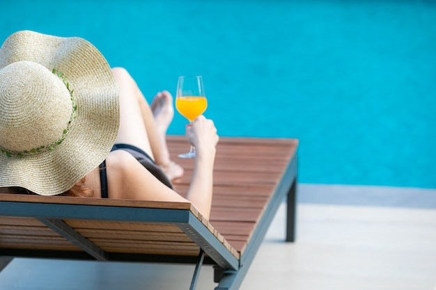 大きな帽子をかぶった女性は、青い水とプールの横にある木製のベッドに横たわっていた。彼女の近くにオレンジジュースのグラスがあります。