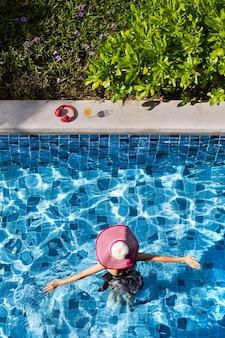 女性は大きな帽子をかぶって腕を広げ、プールを歩いてオレンジジュースと赤いヘッドフォンのグラスに行きます。