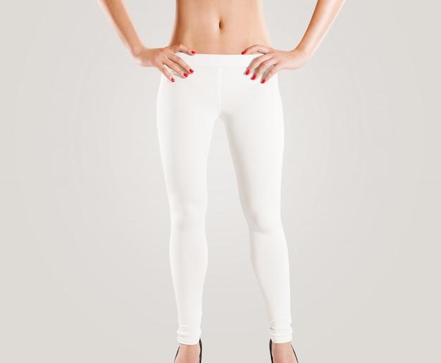 女性は灰色に分離された空白の白いレギンスを着用
