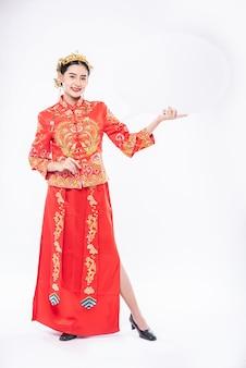 女性はチャイナドレスと黒の靴を履いて、中国の旧正月に驚くべき新しいものを手に入れて喜んで