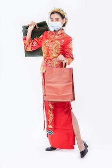 여자는 중국 새해에 쇼핑에서 치파오 양복과 마스크를 들고 종이 봉지를 착용